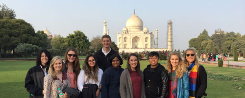 Student group posing in front of structure with Dr. Mary Savin during India Faculty-Led Study Abroad program.